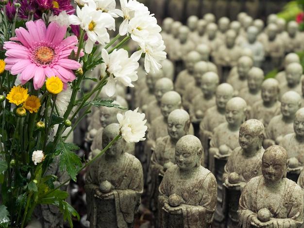 Fileiras de esculturas japonesas semelhantes de jizo no templo hase-dera, kamakura, japão, com foco em flores