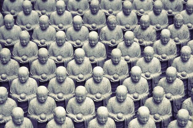 Fileiras de esculturas japonesas semelhantes de jizo no templo hase-dera, kamakura, japão