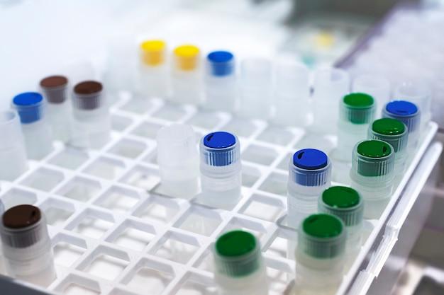 Fileiras de frascos de plástico na bandeja do dispensador automático de líquidos. equipamentos químicos de laboratório. profundidade superficial de campo.
