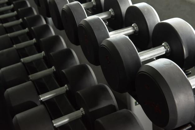 Fileiras de halteres usados para exercer no ginásio de treinamento.