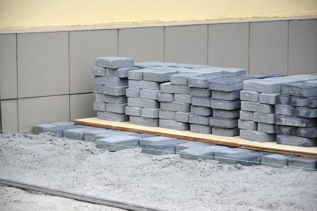 Fileiras de laje de passagem cinza e cinza escuro ao ar livre. material para lajes de pavimentação por mosaico em andamento