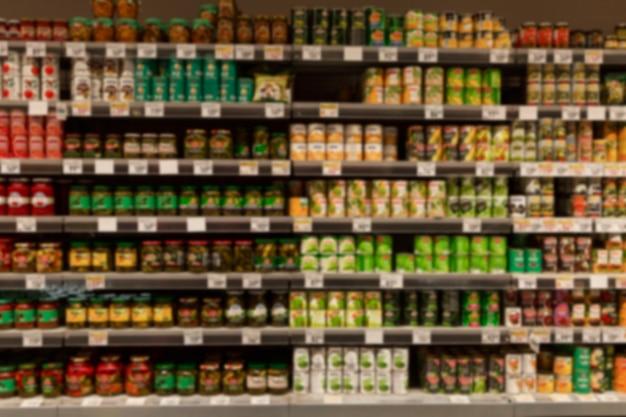 Fileiras de latas de comida enlatada nas prateleiras da loja. vista frontal. borrado.