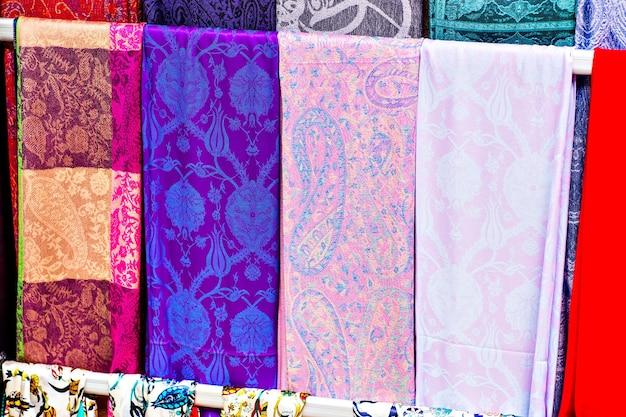 Fileiras de lenços de seda coloridos pendurados em uma barraca de mercado em istambul, turquia