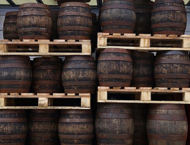 Fileiras de paletes com barris de cerveja artesanal em madeira de carvalho escuro vintage de grunge antigo no armazém da cervejaria