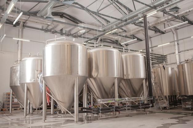 Fileiras de tanques de metal de cerveja na microcervejaria, copie o espaço