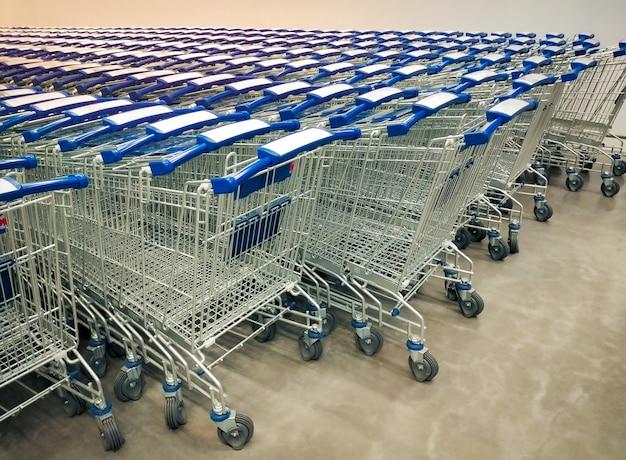 Fileiras dos carrinhos de compras recolhidas no supermercado.