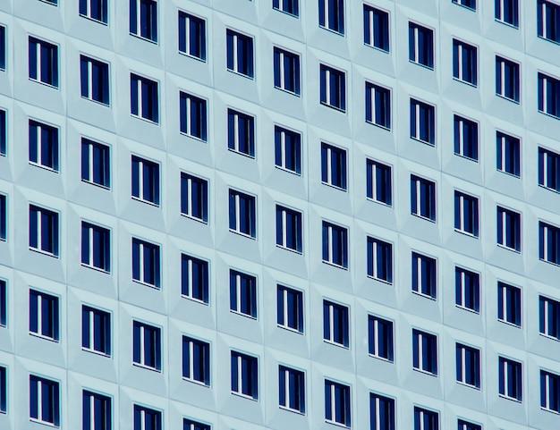 Fileiras retas de janelas em um prédio azul e branco