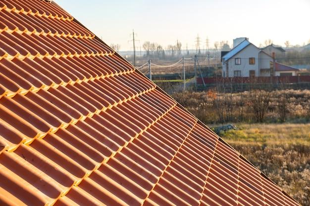 Fileiras sobrepostas de telhas de cerâmica amarela cobrindo o telhado de edifícios residenciais.
