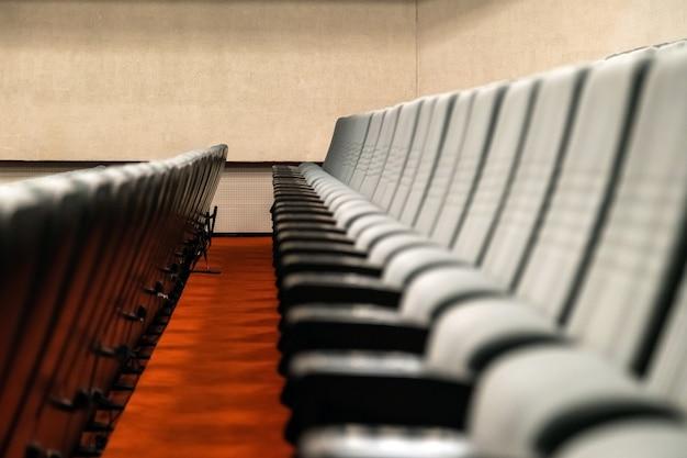 Fileiras vazias de assentos confortáveis de cinema ou teatro.