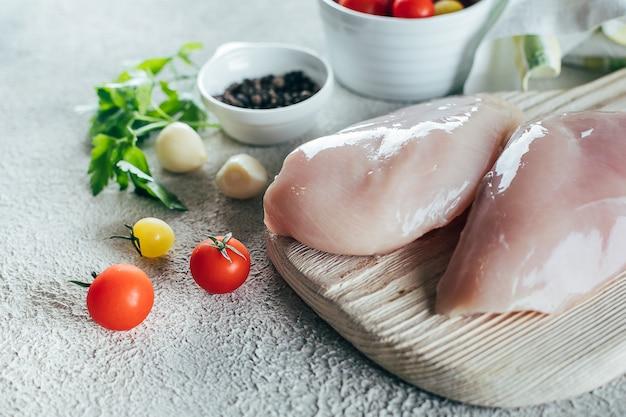 Filés de peito de frango cru e ingredientes para o jantar na placa de madeira no fundo da mesa de concreto