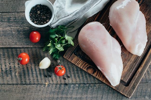 Filés de peito de frango cru e ingredientes para o jantar na placa de madeira no fundo da tabela