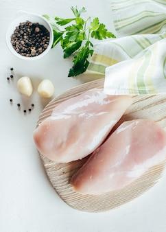 Filés de peito de frango cru na placa de madeira no fundo da tabela