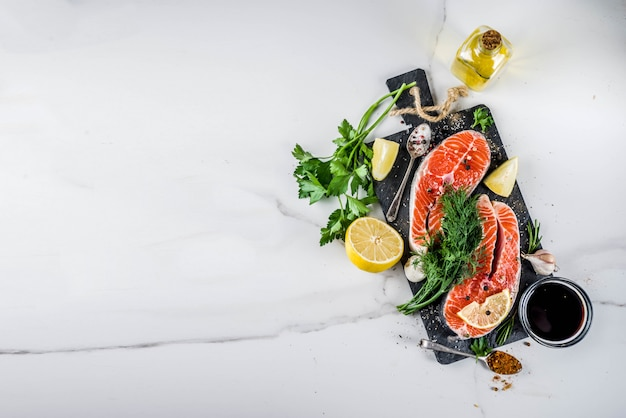 Filés de salmão cru com limão, ervas, azeite, pronto para grelhar, tábua de ardósia, mesa de mármore branco acima