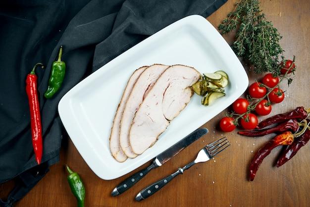 Filete de peru fatiado cozido em um fumeiro (fumante) em um prato branco sobre uma mesa de madeira em uma composição com ingredientes