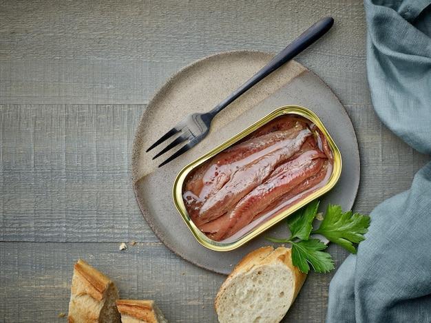 Filetes de anchovas em conserva e fatias de baguete na mesa de madeira da cozinha, vista de cima