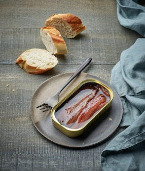 Filetes de anchovas em conserva e fatias de baguete na mesa de madeira da cozinha