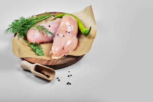 Filetes de frango crus no prato de madeira com colher