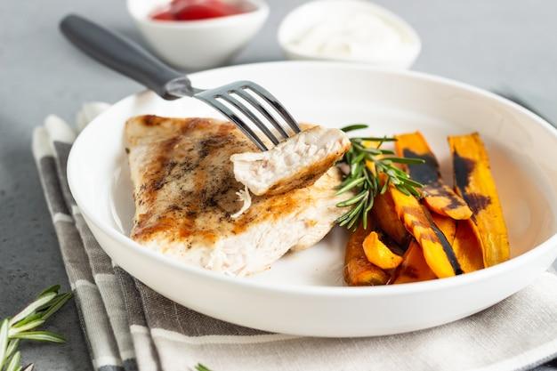 Filetes de frango ou de peru grelhados (bifes), cenoura assada e alecrim em um prato branco