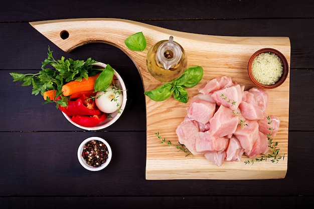 Filetes de peito de frango cru na tábua de madeira com ervas e especiarias. vista do topo