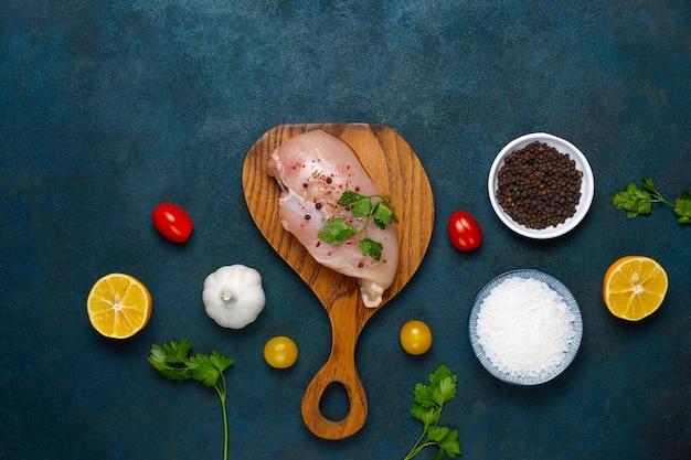Filetes de peito de frango cru na tábua de madeira com ervas e especiarias. vista superior