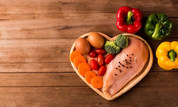 Filetes de peito de frango cru sem desossado com alecrim de especiarias no prato coração