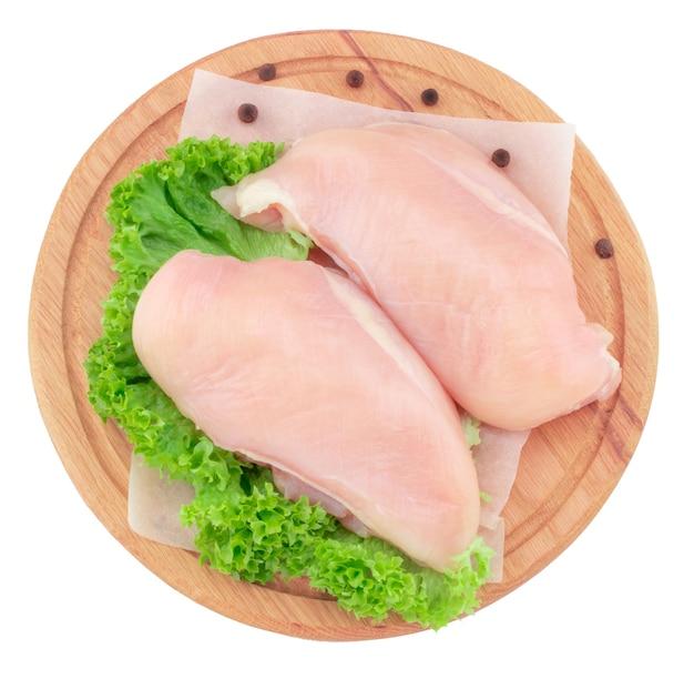 Filetes de peito de frango crus na tábua de madeira isolados