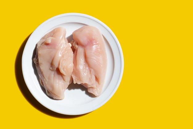 Filetes de peito de frango crus não cozidos em chapa branca sobre fundo amarelo.