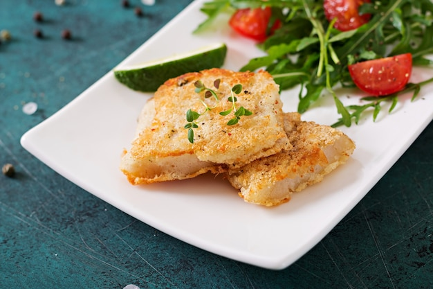 Filetes de peixe branco frito e salada de tomate com rúcula.