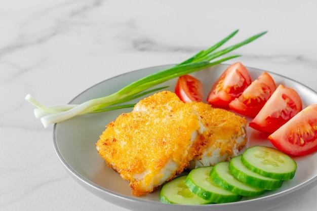 Filetes de peixe frito à milanesa com tomate formiga pepino servido em um prato close-up.