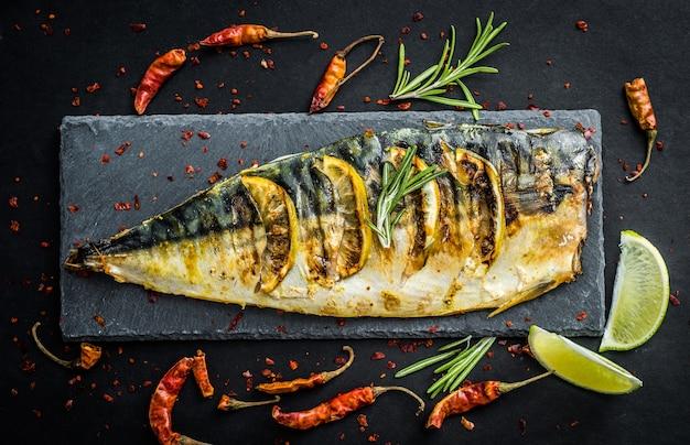 Filetes de peixe grelhado com limão no quadro de ardósia preta, temperado com vegetais e ervas