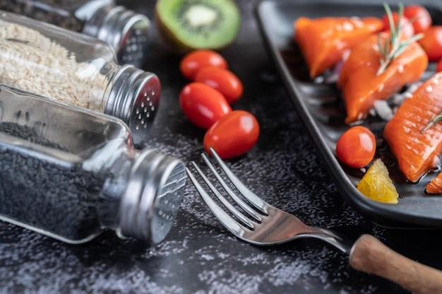 Filetes de salmão cru, pimenta, kiwi, abacaxi e alecrim em um prato e piso de cimento preto.