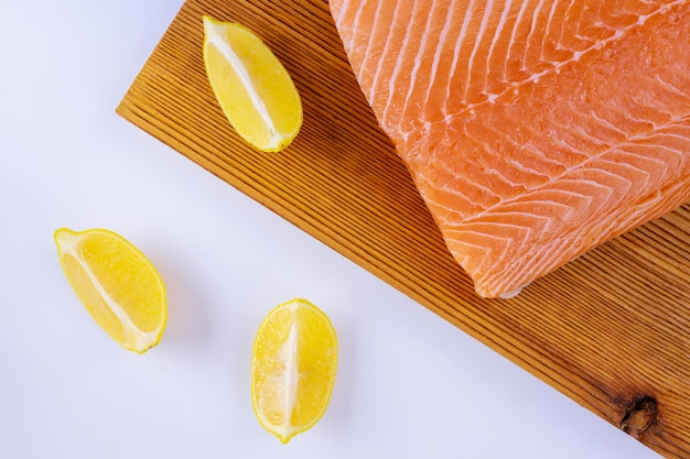 Filetes de salmão crus em tábua de madeira em branco