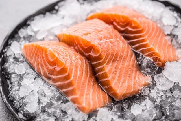 Filetes de salmão crus repartidos no gelo no prato - close-up.