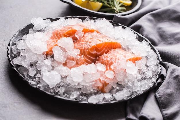 Filetes de salmão crus repartidos no gelo no prato com limão e alecrim.