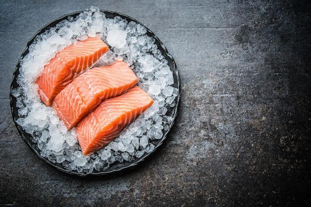 Filetes de salmão crus repartidos no gelo no prato - topo da vista.
