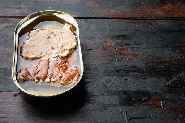Filetes de truta defumada em lata, em lata, na velha mesa de madeira escura