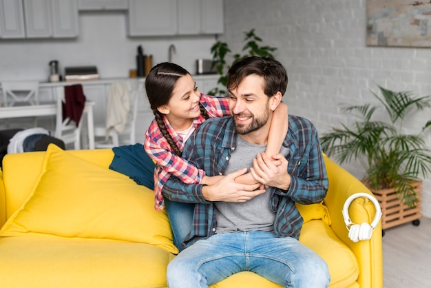 Filha, abraçando o pai na sala de estar