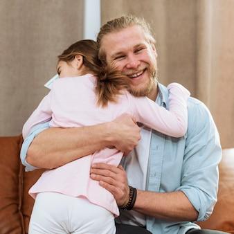Filha abraçando o pai sorridente