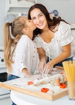 Filha adorável beija sua mãe