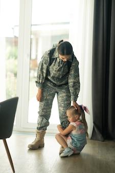 Filha adorável. mulher de cabelos escuros servindo nas forças armadas tocando sua linda filha, sem deixá-la ir