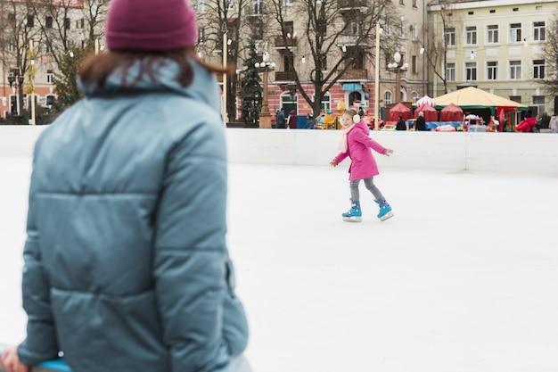 Filha adorável patinar no gelo ao ar livre
