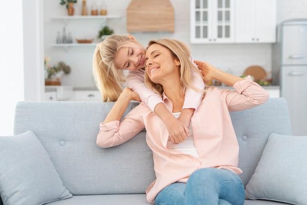 Filha adorável que abraça sua mãe