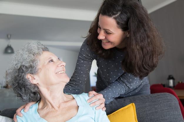 Filha adulta feliz visitando a mãe idosa