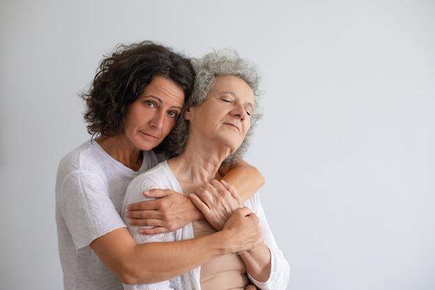 Filha adulta pensativa, abraçando a mãe sênior