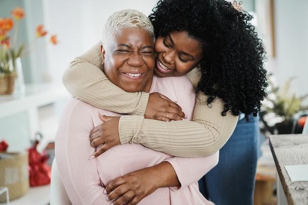 Filha africana abraçando a mãe dentro de casa - foco principal no rosto da mulher idosa