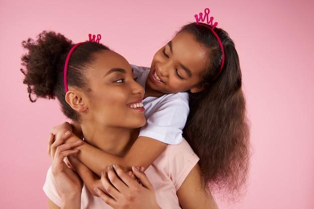 Filha afro-americana e mãe em coroas falsas