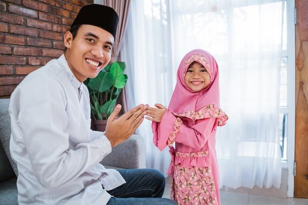 Filha agitar as mãos para seu pai no eid mubarak