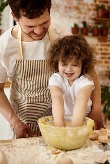 Filha ajuda o pai na cozinha
