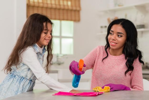 Filha, ajudando a mãe a limpar
