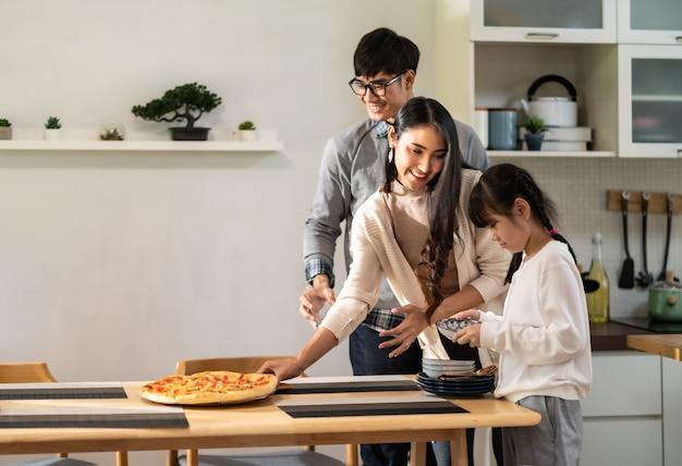 Filha ajudando a mãe e o pai a arrumar a mesa de jantar antes da refeição